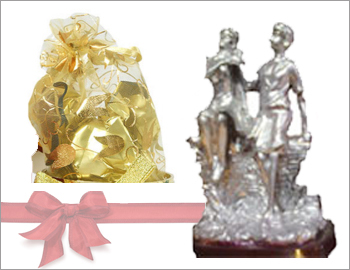 Gift article  with a bag of chocolates: Gift this combination of a gift article depicting boy and girl sculptures (around six inches height) made of gun metal and a bunch of six imported chocolates.
